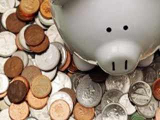 white piggy bank surrounding by coins