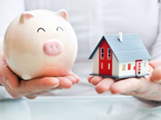 woman holding piggy bank and house