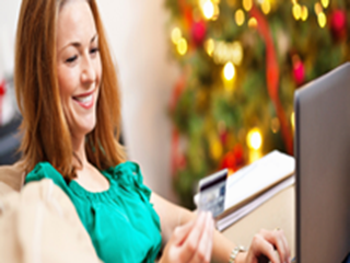 woman shopping online with christmas tree in background
