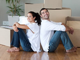 happy couple sitting on floor surrounded by boxes