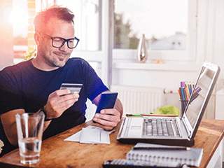 man holding bank card looking at phone