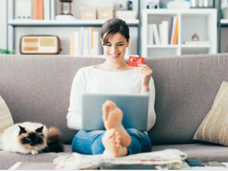 smiling woman sitting on sofa holding bank card looking at laptop