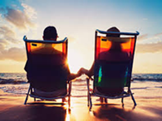 couple sitting in deck chairs at the beach at sunset