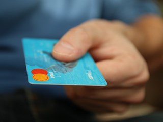 man holding blue bank card