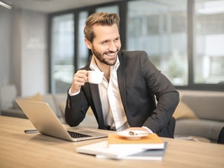 smiling businessman holding coffee cup