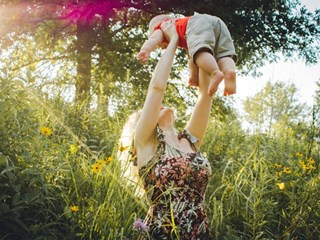 woman lifting baby in the air