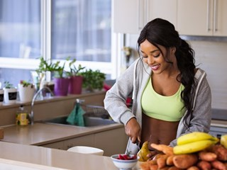 athletic woman chopping up fruit