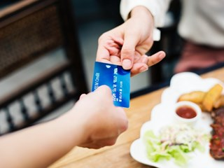 woman handing over card to pay in restaurant