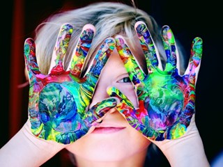 child holding up hands covered in paint
