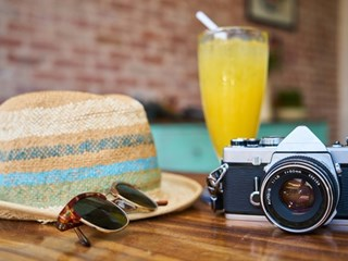 camera hat and sunglasses on wooden table