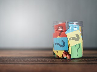 paper with question marks in clear jar