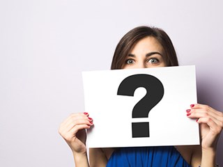 woman holding up paper question mark