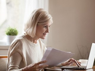 retired woman working on laptop holding documents